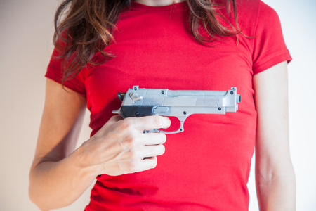 detail close up of woman with red tee shirt with a plastic toy silver false pistol gun in her hand Stock Photo