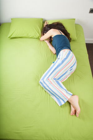 brunette woman in pajama sleeping on green sheets bed with head resting on pillow and hiding eyes under arm Stock Photo