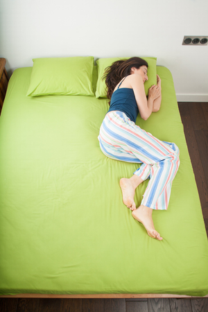 brunette woman in pajama sleeping on green sheets bed with head resting on pillow Stock Photo