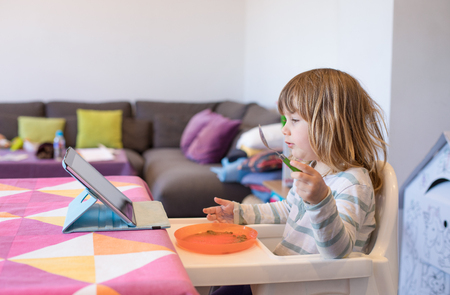 Three years old blonde child sitting in white high chair indoor, eating from orange plastic dish, and watching digital tablet on the table Stock Photo