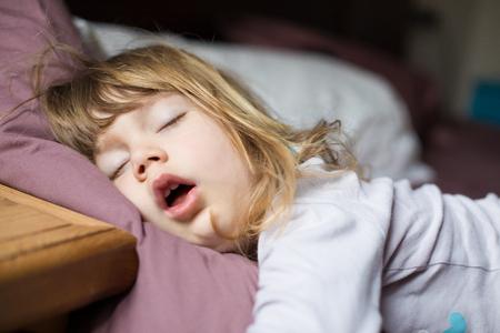 ベッド王で眠っている、金髪の白人の 3 歳子供の口を開けて面白い表情