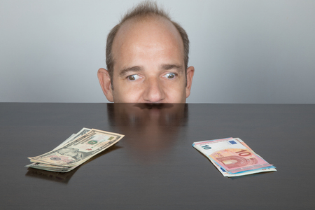 avarice: portrait of caucasian adult man face peering over dark brown table. One eye looking at Dollar and other at Euro pile of banknotes, like squint eyes or exotropia Stock Photo