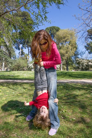 three years old blonde child laughing face, upside down, hanging from woman mother hands, playing on green grass field in public park