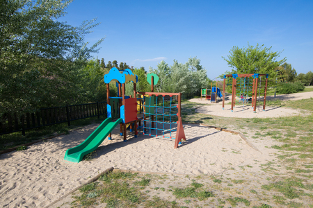 plastic two swing sets on earth sand ground in playground with slide in public Park Valdebebas in Madrid city, Spain Europe