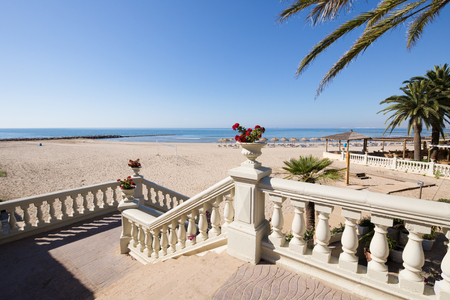 Scale classiche con vasi con fiori e palme, verso la spiaggia pubblica di sabbia di Voramar, a Benicassim, Castellon, Valencia, Spagna, Europa. Cielo blu chiaro e Mar Mediterraneo Archivio Fotografico - 82665448