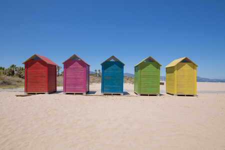five wooden bathing cabins or huts, colored in blue, red, pink, yellow and green, and wooden footway on sand, Beach of PIne or Pinar, Grao Castellon, Valencia, Spain, Europe. Blue sk Stok Fotoğraf