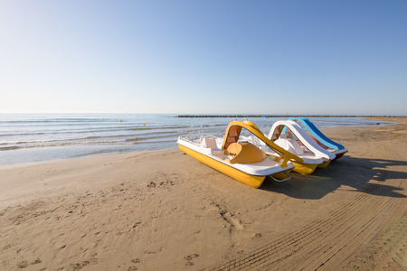 three pedal boats in row on the beach Els Terrers, in Benicassim, Castellon, Valencia, Spain, Europe. Blue clear sky and Mediterranean Sea Stock Photo