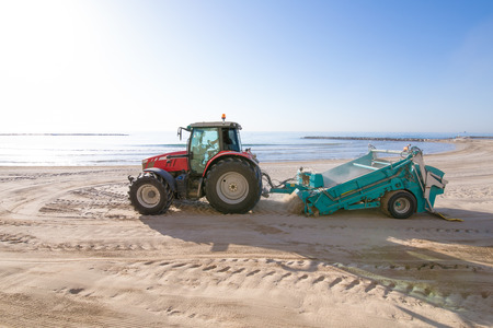 red tractor with trailer cleaner cleaning sand in Els Terrers Beach, Benicassim, Castellon, Valencia, Spain, Europe. Mediterranean Sea Stock Photo