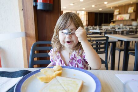funny portrait of blonde three years old child, playing with a spoon over eyes, hiding face, and bread toast in dish, sitting indoor in restaurant
