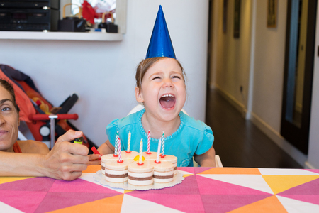 three years old blonde child with blue shirt and cone hat, and birthday cake with candles on colorful tablecloth, screaming angry, next to woman with lighter in hand