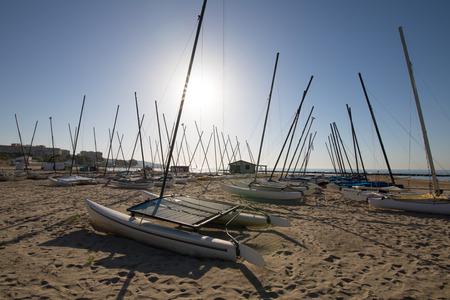 groep van catamaran boten in de zon op het strand Els Terrers, in Benicassim, Castellon, Valencia, Spanje, Europa. Blauwe heldere lucht en de Middellandse Zee