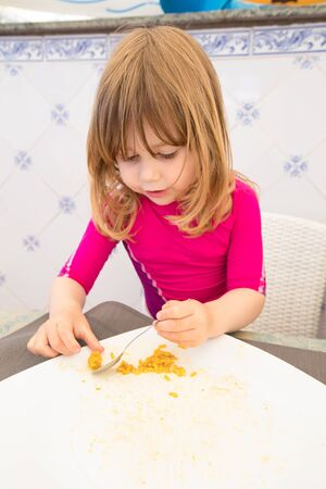 three years old blonde child with red shirt eating with spoon and finishing Spanish paella rice in big white plate