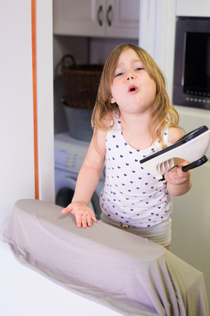 four years old blonde child with white shirt in the kitchen, ironing clothes and looking complaining