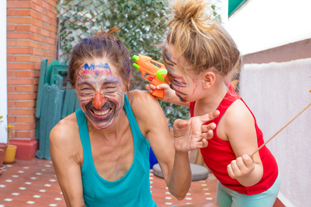 happy family with painted faces, three years old child with orange plastic water gun and woman laughing, in terrace of house Stock Photo