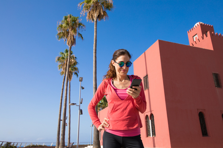woman with red sweater smiling and using mobile phone next to Bil Bil Tower, in the promenade of Benalmadena, Malaga, Andalusia, Spain