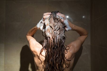 female in douche: adult woman from behind washing her brunette long hair with shampoo and two hands in shower with brown marble tiles
