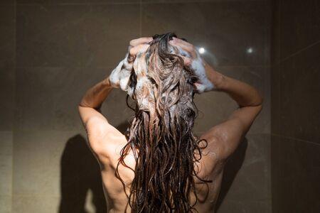 piojos: mujer adulta desde atrás lavando su cabello largo morena con champú y dos manos en la ducha con azulejos de mármol marrón Foto de archivo