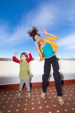Happy three years old blonde girl and woman mother jumping with hands up and looking smiling in terrace Stock Photo
