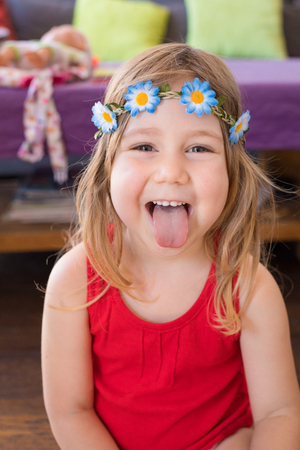 portrait of three years old blonde pretty girl face looking and sticking out tongue, with red sleeveless t-shirt and wreath with flowers, indoor at home
