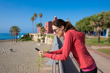 woman with red hoodie using mobile phone resting on railing of promenade next to Bil Bil beach, in Benalmadena, Malaga, Andalusia, Spain Stockfoto