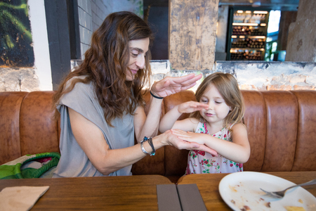 Four years age blonde happy girl playing with hands with woman mother and smiling sitting in brown leather sofa at restaurant