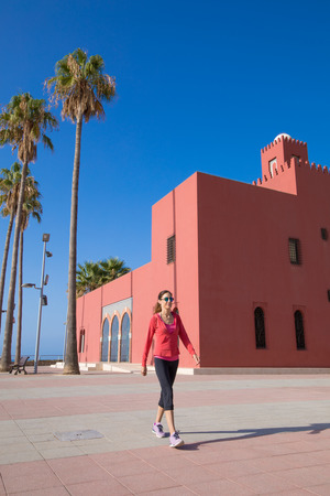 woman with red sweater walking next to Bil Bil Tower, in the promenade of Benalmadena, Malaga, Andalusia, Spain
