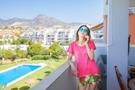 smiling woman, with red shirt and sunglasses, talking on mobile phone in the terrace. Behind pool, grass and houses
