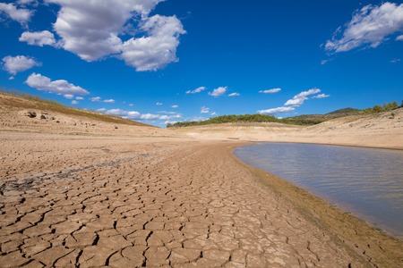 landscape of low level water and dry earth ground in advance, extreme drought in Entrepenas reservoir, in Guadalajara, Castile, Spain, Europe Stock Photo