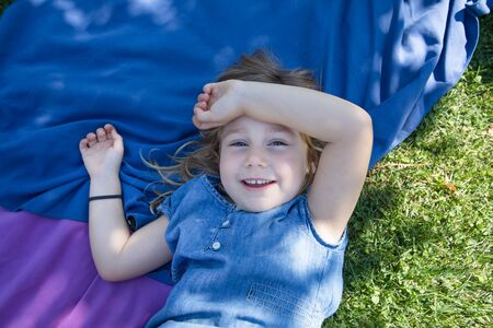 four years old blonde girl lying on towels in the green grass of park with hand in head looking and smiling