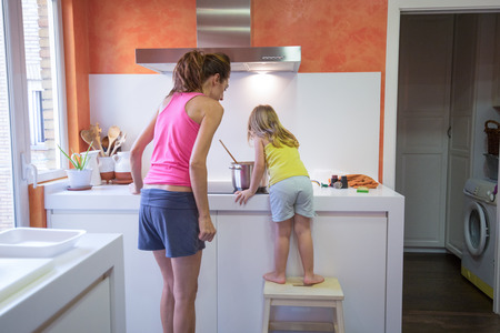 Funny scene. Four years old blonde child climb on stool o ladder cooking in vitroceramic or electric stove with a saucepan, next to woman supervising, in teamwork in the kitchen