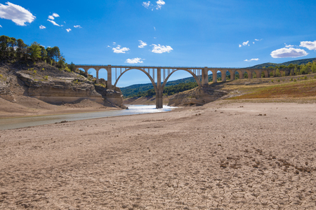 landscape of dry earth ground and bridge, extreme drought in Entrepenas reservoir, in Guadalajara, Castilla, Spain Europe