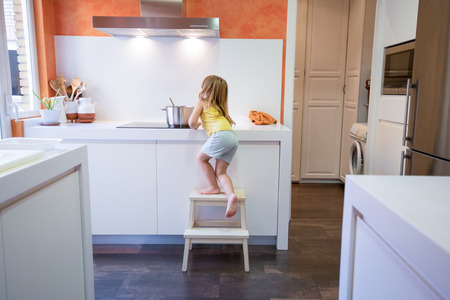 Four years old blonde child climbing on stool o ladder to cook in electrical cooktop with a saucepan, alone in the kitchen