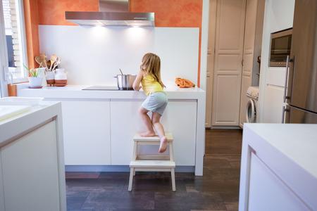 Niño rubio de cuatro años que sube en taburete o escalera para cocinar en estufa eléctrica con una cacerola, solo en la cocina Foto de archivo