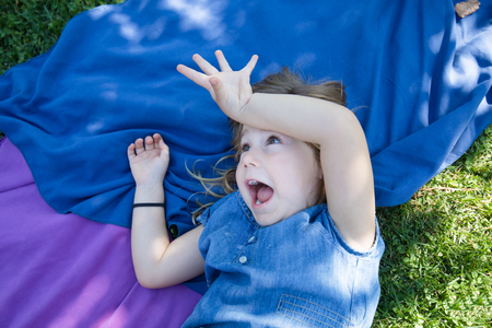 four years old blonde girl lying on towels in the green grass of park with hand in head laughing with funny expression face teasing