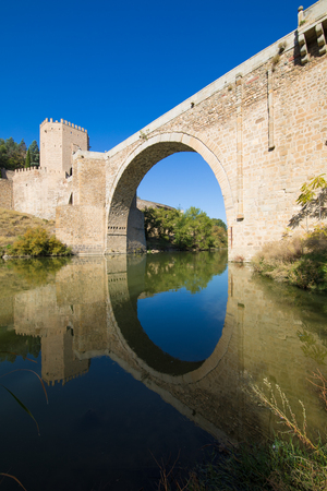 arch of Alcantara bridge, landmark and monument from ancient Roman age, reflected on water of river Tagus, Tajo in Spanish, in Toledo city, Spain, Europe