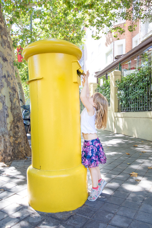 little girl with skirt on tiptoes throwing a letter in a yellow mailbox on a street of Madrid city