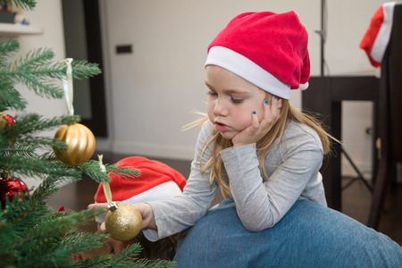 funny scene: four years blonde cute girl with red Santa Claus hat, holding a golden ball in Christmas tree, resting on her mother back, at home Stock Photo - 92558762