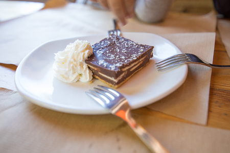 square piece of brown chocolate cake with cream on white ceramic dish, with three forks for sharing, on paper placemats and wooden table