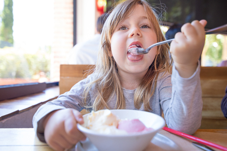 portrait of three years old blonde child eating with spoon two scoops of strawberry and vanilla ice cream, in white bowl, sitting at the restaurant table