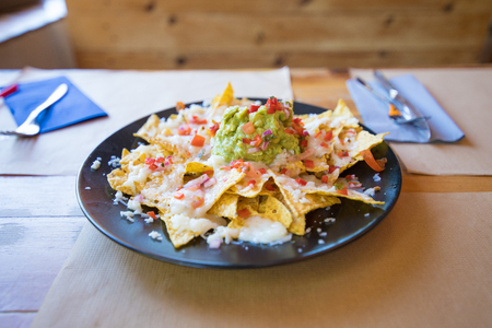 black plate with nachos and guacamole, chopped tomato and cheese, on wooden table with paper placemats at restaurant