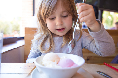 portrait of three years old blonde child ready to eat two scoops of strawberry and vanilla ice cream, in white bowl, with a spoon in raised hand, sitting at the restaurant table
