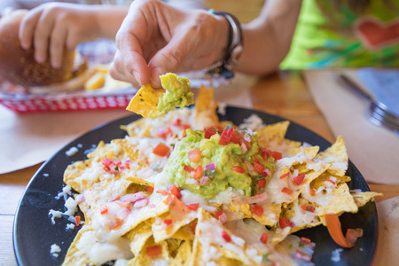 woman hand dipping nacho chips in avocado guacamole, cheese and chopped tomato on black plate, on wooden table with paper placemats at restaurant