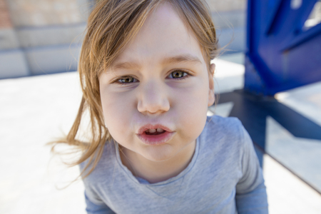 close up portrait of three years old child face, with grey shirt, looking at complaining and gesturing mouth