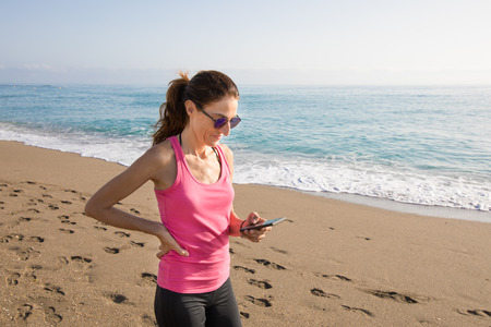woman with pink sleeveless t-shirt smiling and touching mobile phone smartphone at beach with sea and buildings behind in Benalmadena, Malaga, Andalusia, Spain. Big copy space in sea Stock Photo