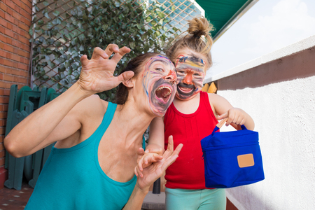 portrait of happy family, woman and three years old child painted faces, looking smiling and making grin, in terrace of house