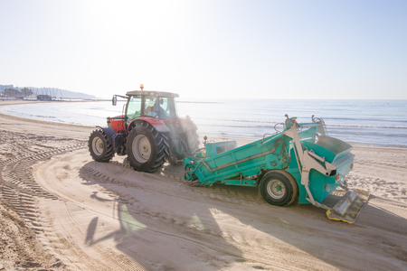 red tractor with green trailer cleaner cleaning sand in Els Terrers Beach, Benicassim, Castellon, Valencia, Spain, Europe. Mediterranean Sea Stockfoto