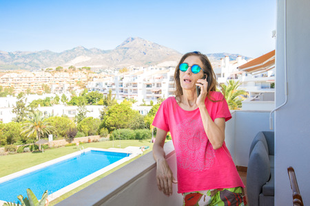 woman with red shirt and sunglasses, talking on mobile phone in the terrace. Behind pool, grass and houses Stock Photo