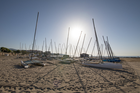many catamarans in the sun on the beach Els Terrers, in Benicassim, Castellon, Valencia, Spain, Europe. Blue clear sky and Mediterranean Sea