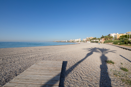 landscape with shadow of two palm trees on pebbles of a Els Terrers Beach, in Benicassim, Castellon, Valencia, Spain, Europe. Wooden boardwalk, buildings, blue clear sky and Mediterranean Sea