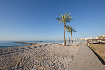 landscape Els Terrers Beach, in Benicassim, Castellon, Valencia, Spain, Europe. Palm trees, wooden walkway, buildings, blue clear sky and Mediterranean Sea Stock Photo